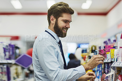 Buy stock photo Cropped shot of a handsome young man looking for medication in a pharmacy