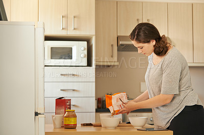 Buy stock photo Cropped shot of a beautiful young woman making breakfast in the kitchen at home