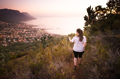 Buy stock photo Rearview shot of a young woman out on a hike through the mountains