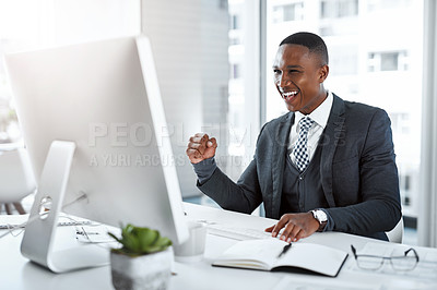 Buy stock photo Shot of a young businessman using a computer and cheering at his desk in a modern office