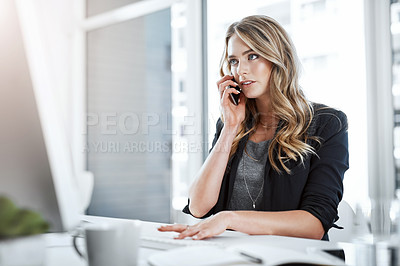 Buy stock photo Shot of a young businesswoman using a mobile phone and computer at her desk in a modern office