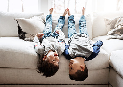 Buy stock photo Shot of two adorable brothers playing together on the sofa at home