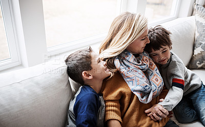 Buy stock photo Shot of two adorable little boys bonding with their mother on the sofa at home
