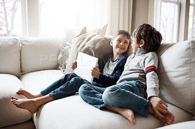 Buy stock photo Shot of two adorable brothers using a digital tablet together while relaxing on the sofa at home