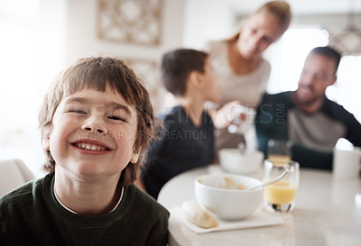 Buy stock photo Portrait of a happy little boy enjoying breakfast together with his family at home