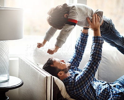Buy stock photo Shot of an adorable little boy having fun with his father on the sofa at home