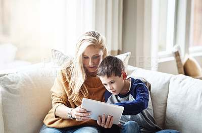 Buy stock photo Shot of an adorable little boy using a digital tablet with his mother while relaxing on the sofa at home