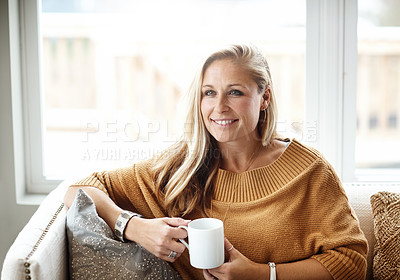Buy stock photo Shot of a happy woman drinking a beverage while relaxing on the sofa at home