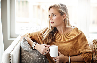 Buy stock photo Shot of a thoughtful woman drinking a beverage while relaxing on the sofa at home