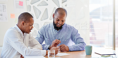 Buy stock photo Shot of two businessmen going through some paperwork in an office