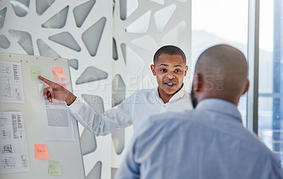 Buy stock photo Shot of a businessman giving a presentation to his colleague in an office