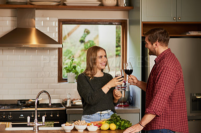 Buy stock photo Shot of a young couple drinking wine while cooking together at home