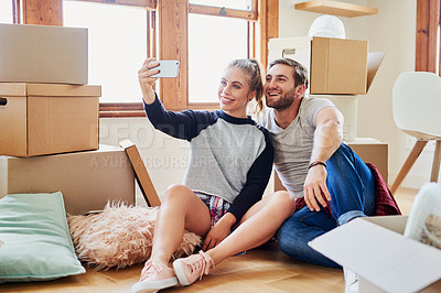 Buy stock photo Shot of a happy young couple taking a selfie in their new home