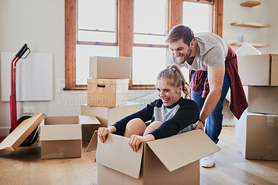 Buy stock photo Cropped shot of a happy young couple being playful with boxes in their new home