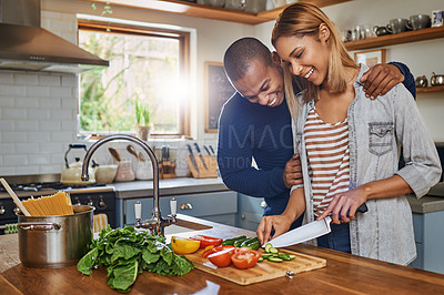 Buy stock photo Shot of a young man embracing his girlfriend while she's busy preparing food