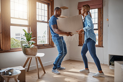 Buy stock photo Shot of a young couple carrying a cardboard box in their new house