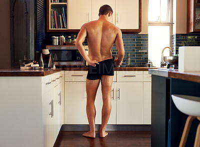 Buy stock photo Rearview shot of an unrecognizable shirtless man making breakfast in the kitchen at home