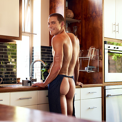 Buy stock photo Cropped shot of a handsome young shirtless man preparing to make breakfast in the kitchen at home