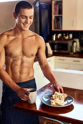 Buy stock photo Cropped shot of a handsome young shirtless man having breakfast in the kitchen at home