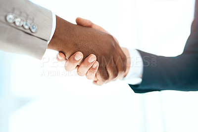 Buy stock photo Cropped shot of two unrecognizable business colleagues shaking hands in their office