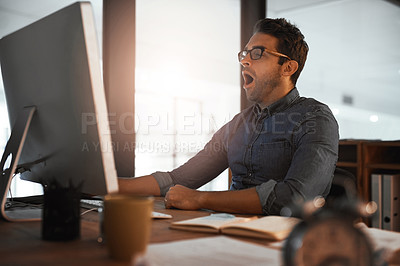 Buy stock photo Shot of a young businessman yawning while working late on a computer in an office