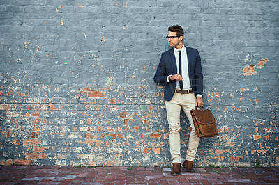 Buy stock photo Full length shot of a handsome young businessman standing against a grey facebrick wall