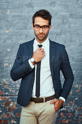 Buy stock photo Cropped portrait of a handsome young businessman adjusting his tie while standing against a grey facebrick wall