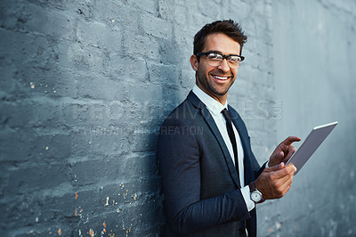 Buy stock photo Cropped portrait of a handsome young businessman using his tablet while standing against a grey facebrick wall