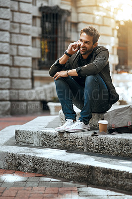 Buy stock photo Full length shot of a handsome young man making a phonecall while traveling through the city