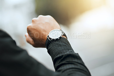 Buy stock photo Cropped shot of an unrecognizable man checking the time while traveling through the city