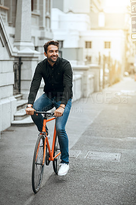 Buy stock photo Full length shot of a handsome young man traveling through the city by bike