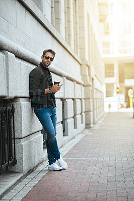 Buy stock photo Full length shot of a handsome young man sending a text while traveling through the city