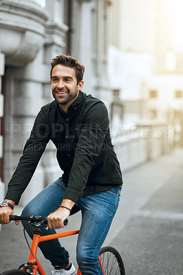 Buy stock photo Cropped shot of a handsome young man traveling through the city by bike