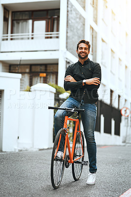 Buy stock photo Full length portrait of a handsome young man traveling through the city by bike