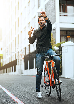 Buy stock photo Full length shot of a handsome young man taking selfies while traveling through the city by bike