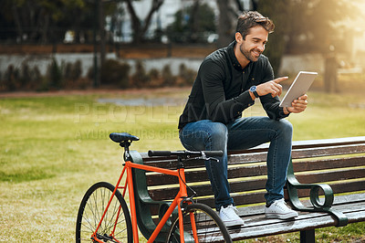 Buy stock photo Full length shot of a handsome young man using his tablet while sitting on a park bench