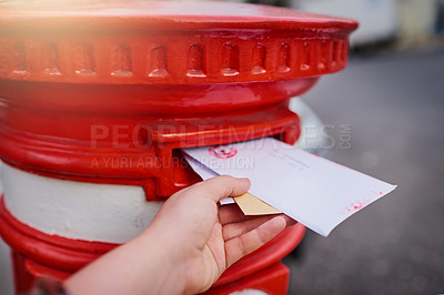 Buy stock photo Closeup of an unrecognizable person's hand sliding in letters into a red mailbox outside during the day