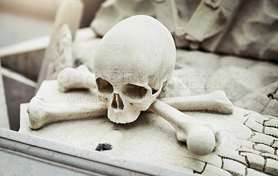 Buy stock photo Closeup of a skull statue on a grave at a graveyard outside during the day