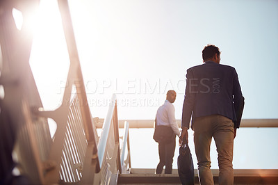 Buy stock photo Low angle shot of unrecognizable businessmen walking up stairs outside