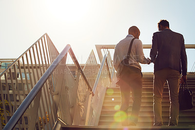 Buy stock photo Rearview shot of unrecognizable businessmen walking up stairs outside