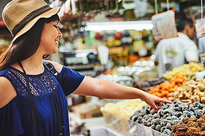 Buy stock photo Shot of a cheerful young woman browsing through a market deciding what to buy outside during the day