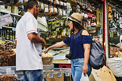 Buy stock photo Shot of a carefree young woman browsing through a market while talking to a man about his products he's selling