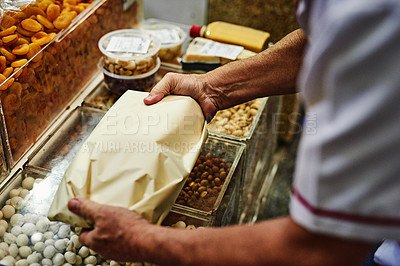 Buy stock photo Shot of an unrecognizable man packing up goods into a paper bag to give to a customer at a market during the day
