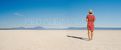 Buy stock photo Rearview shot of a young woman walking barefoot in the desert