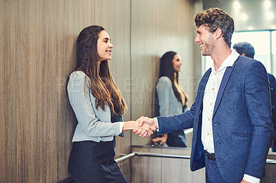 Buy stock photo Cropped shot of a businessman and businesswoman greeting by handshake in an elevator