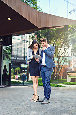 Buy stock photo Shot of a businessman and businesswoman using a tablet outside