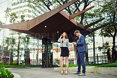 Buy stock photo Shot of a businesswoman on a call and a businessman using a cellphone outside