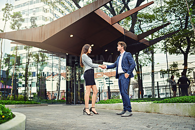 Buy stock photo Shot of a businesswoman and businessman shaking hands outside