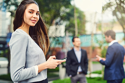 Buy stock photo Cropped shot of a beautiful young businesswoman using a cellphone outside