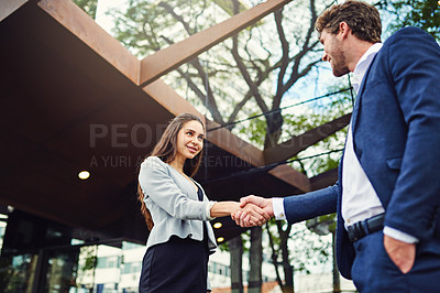 Buy stock photo Cropped shot of a businesswoman and businessman shaking hands outside